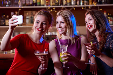bar drinks: Lovely girls are taking a selfie in the bar