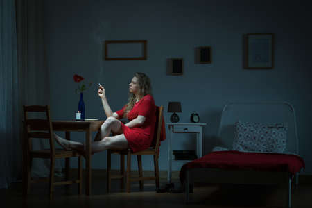 man in chair: Young woman is waiting in the night for her man Stock Photo