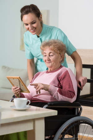 nursing treatment: Senior smiling lady showing the picture to her young pretty nurse