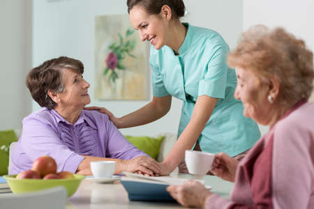 enfermeras: Dos mujeres mayores que tienen una agradable conversaci�n con la joven enfermera Foto de archivo
