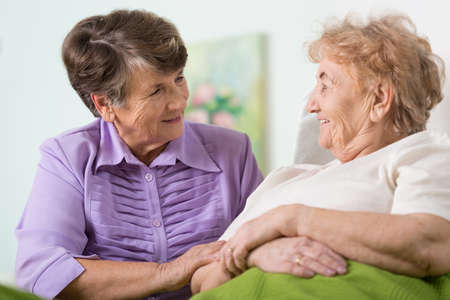elderly: Happy elder woman spending time with her ill friend Stock Photo
