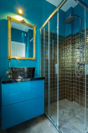 golden: Blue fashionable bathroom with golden tiles in shower