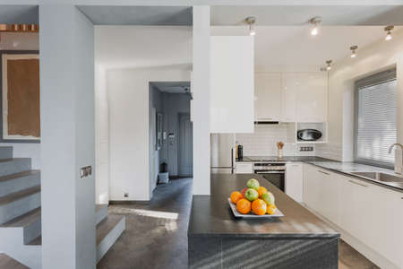 Small white luxurious kitchen with marble black counter