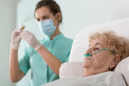 젊은 예쁜 간호사가 그녀의 환자에 주입 할 준비 스톡 콘텐츠