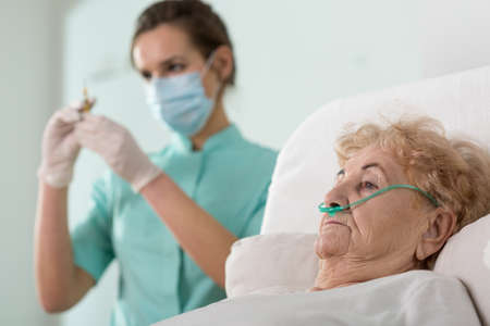 enfermera: Enfermera bonita joven que se prepara para hacer la inyección a su paciente