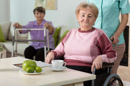 Older disabled woman on wheelchair in nursing home Stock Photo