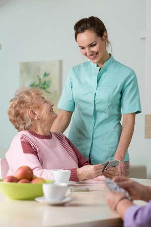 Jonge mooie verpleegster het verzorgen van haar leeftijd vrouwelijke patiënt Stockfoto
