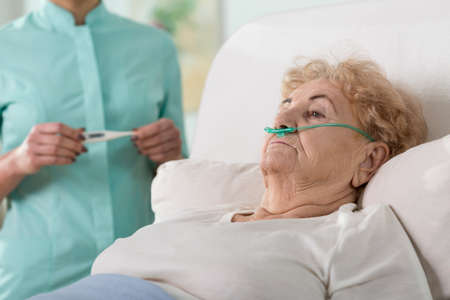 nurse and patient: Sick aged woman lying in hospital bed Stock Photo