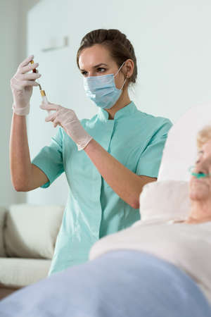 doctor female: Young attractive female doctor doing the inoculation Stock Photo