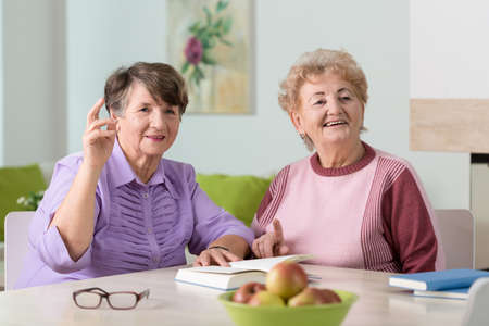 home care: Two happy senior ladies sitting together in lounge