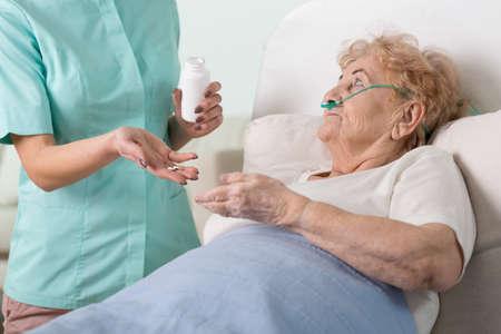 persona mayor: Enfermera joven que da las píldoras a su paciente mayor enfermo Foto de archivo