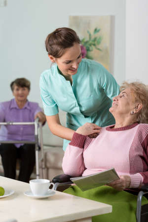 senior old: Young lovely therapist worried about her patient