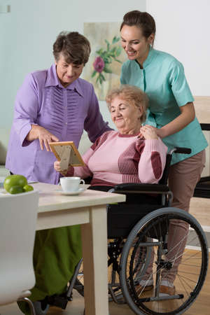 handicapped person: Two senior women and young nurse looking at photo Stock Photo