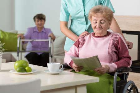 silla de ruedas: Mujer feliz mayor en silla de ruedas que lee el periódico por la mañana