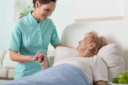 Senior woman in hospital bed holding nurse's hand