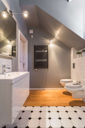 inclined: Small grey modern bathroom with inclined wall