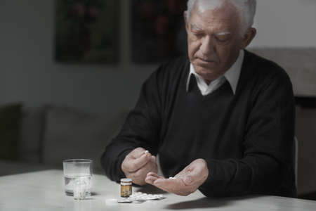take medicine: Senior sad man taking a lot of medicines