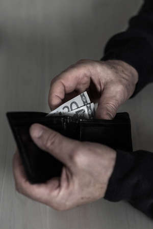 outgoings: Close-up of male hands holding wallet with money