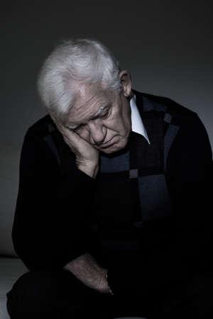 Depressieve oude man zit alleen in de duisternis Stockfoto