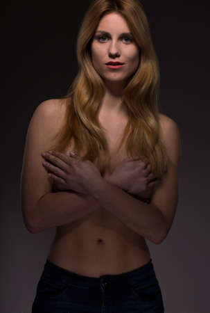 Pretty slim topless girl encasing her breasts