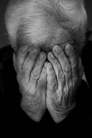 hands covering face: Hands covering face of old depressed man Stock Photo
