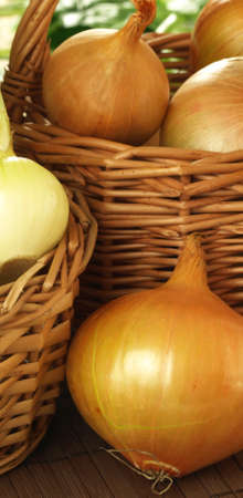 close up of onions in a basket: Vertical photo of onions in wicker basket