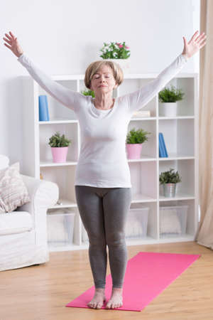 Senior woman taking deep breath during morning yoga