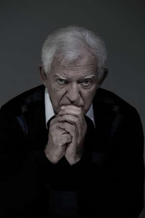 Vertical view of sad senior man praying
