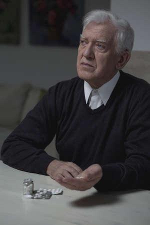 hombre solitario: Hombre solitario mayor que toma medicamento para la depresi�n Foto de archivo