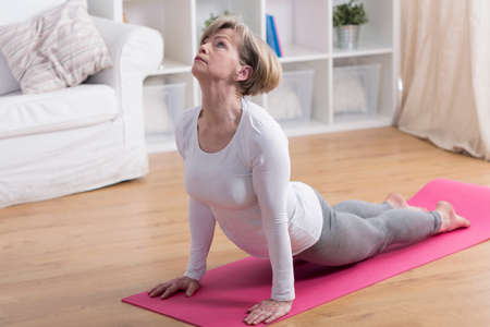 Older active woman exercising yoga in the morning