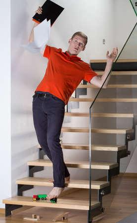 남자는 아파트 계단에 장난감에 미끄러 스톡 콘텐츠