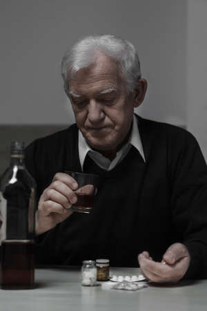 abuser: Addicted retiree drinking whiskey and taking drugs Stock Photo