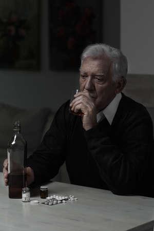 hombre solitario: Solitaria viejo whisky hombre bebiendo y tomando pastillas