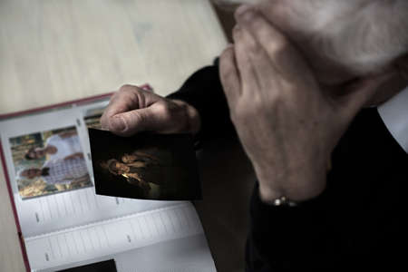Close-up van trieste senior man kijkt familie fotografie