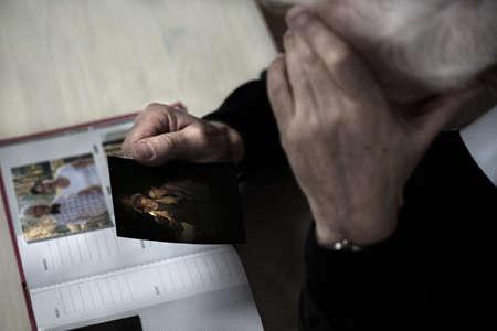 soledad: Primer plano de hombre mayor triste ver fotografía de la familia