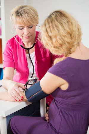 hipertension: Mujer embarazada en la oficina que tiene la presión del doctor medido