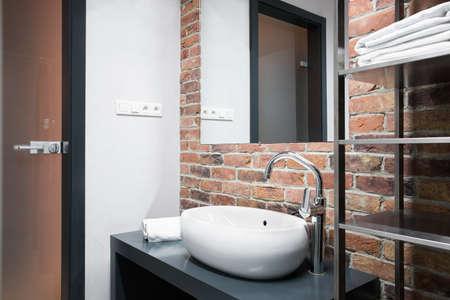 Small modern bathroom with brick wall in home Archivio Fotografico