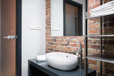 Small modern bathroom with brick wall in home Stock Photo