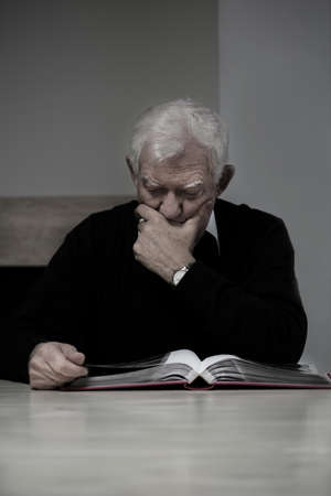 photo album: Old man looking at family photo album