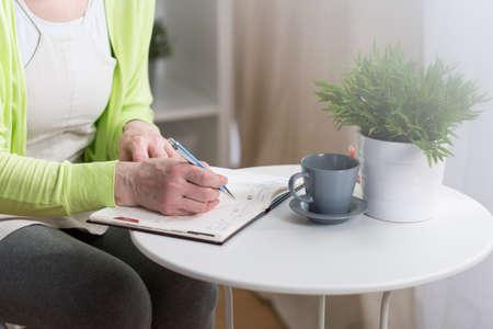 calendario: Primer plano de mujer de edad avanzada que controla su calendario Foto de archivo