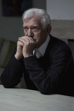prying: Old man sitting at the table and praying Stock Photo