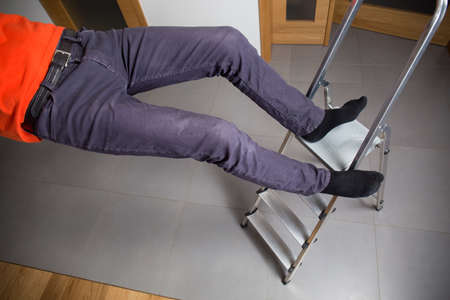 safety at work: Man is falling down from ladder at home Stock Photo