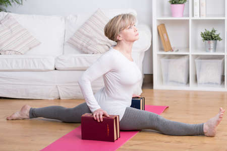 stretched: Stretched retired woman doing splits at yoga exercises Stock Photo