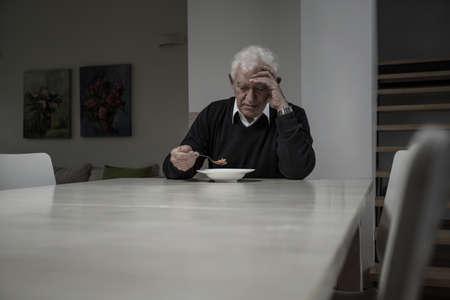 Beeld van de eenzame gepensioneerde man het eten van soep Stockfoto