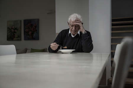 Image of lonely retired man eating soup photo