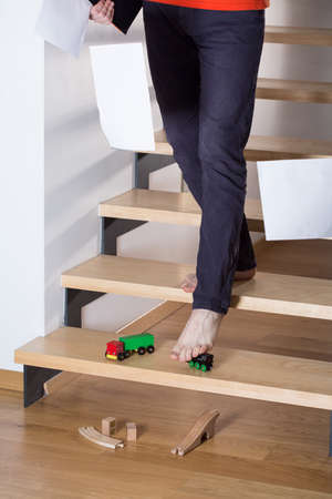 Man slip on a toy left on stairs photo