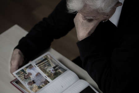 reminisce: Man in mourning looking at photos with wife Stock Photo