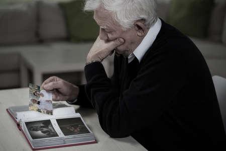 hombre solo: Viudo mirando las fotos y recordar esposa fallecida Foto de archivo