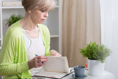 Middle aged organized woman looking at her calendar