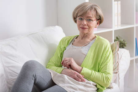 after work: Elderly tired woman resting on couch after work